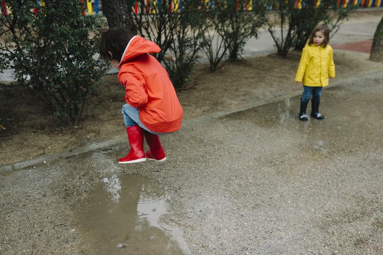 Full length of siblings walking on puddle