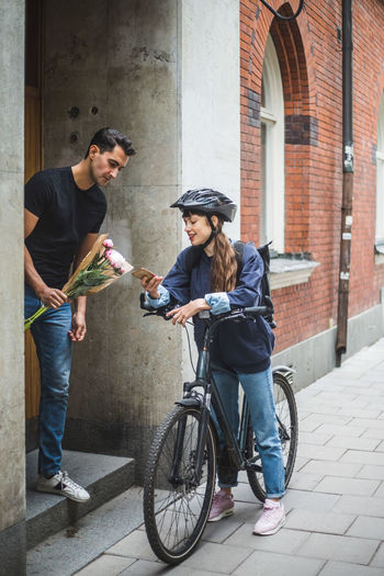 Young couple holding bicycle in city