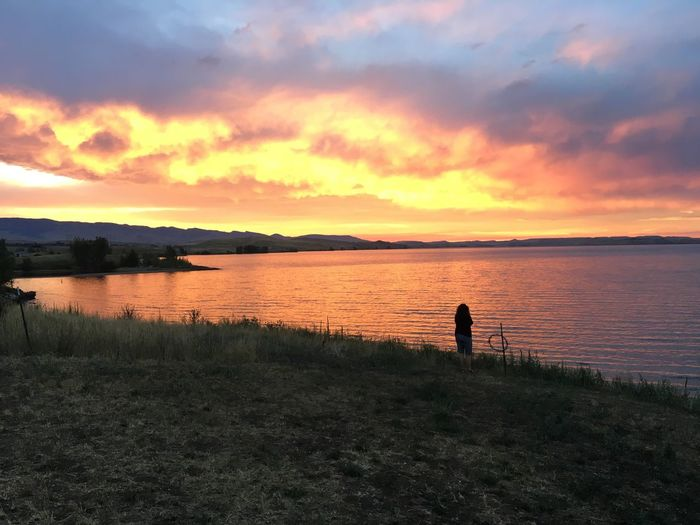 Rear view of woman standing against lake during sunset