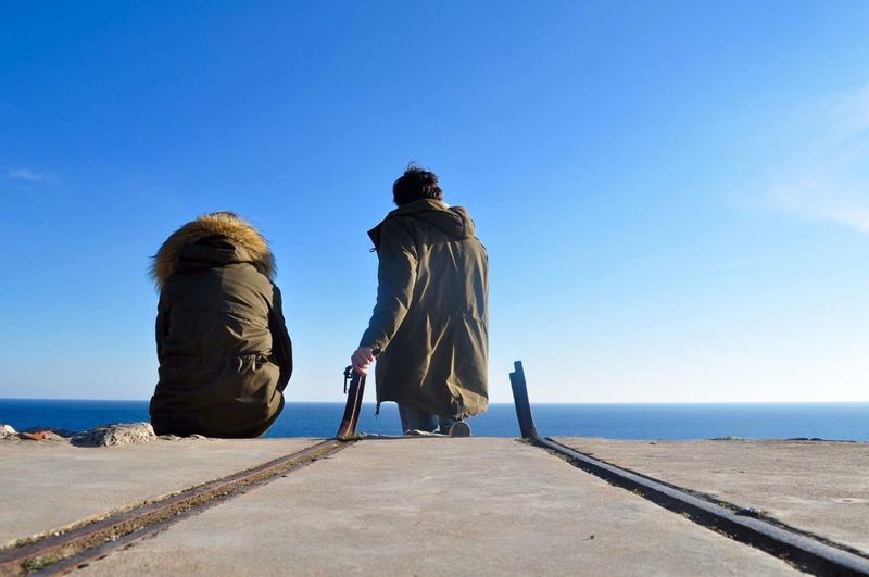 Rear View Of Man And Woman Wearing Warm Clothes While Relaxing Against Sea