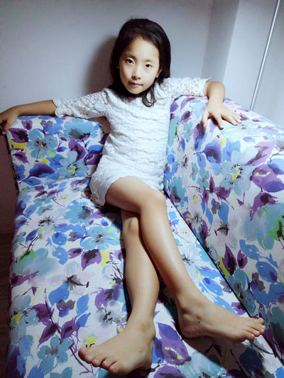 High angle portrait of girl with legs crossed at knee relaxing on sofa at home
