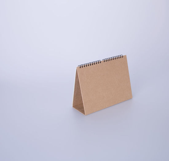 High angle view of blank brown desk calendar on white background