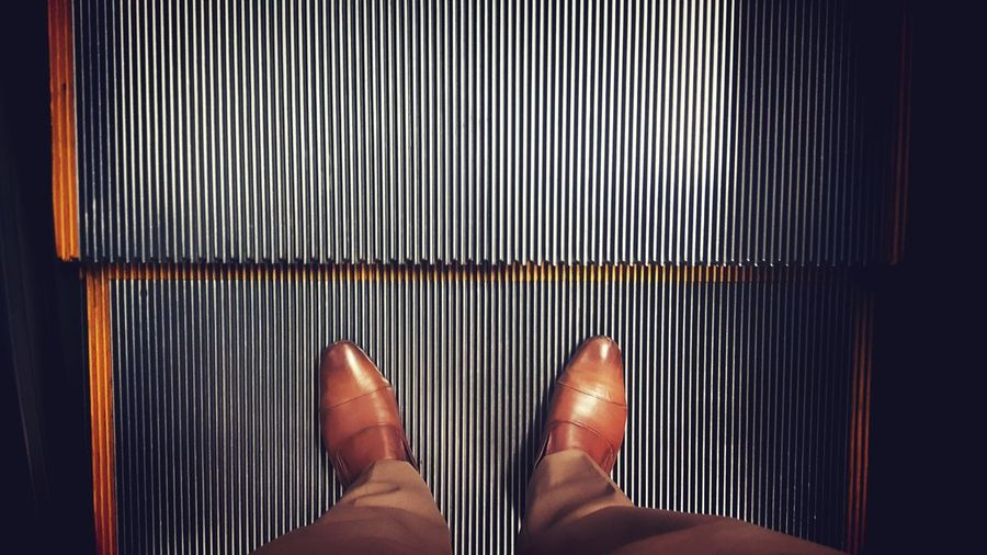 Low section of businessman standing on escalator