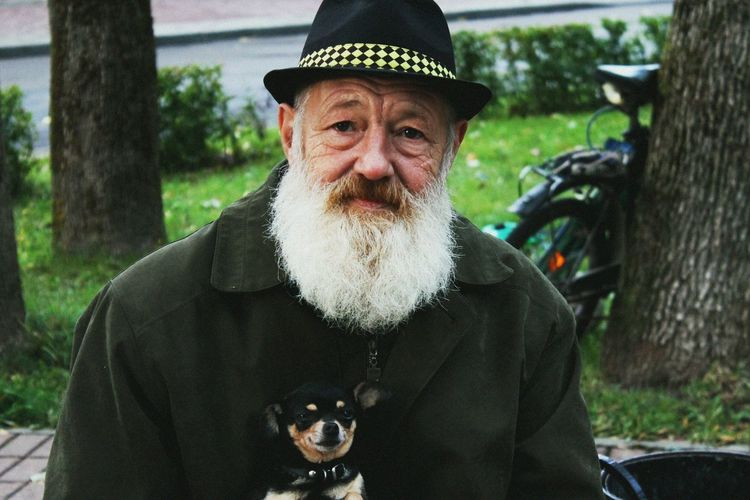 Portrait Of Mature Bearded Man With Dog Sitting In Park