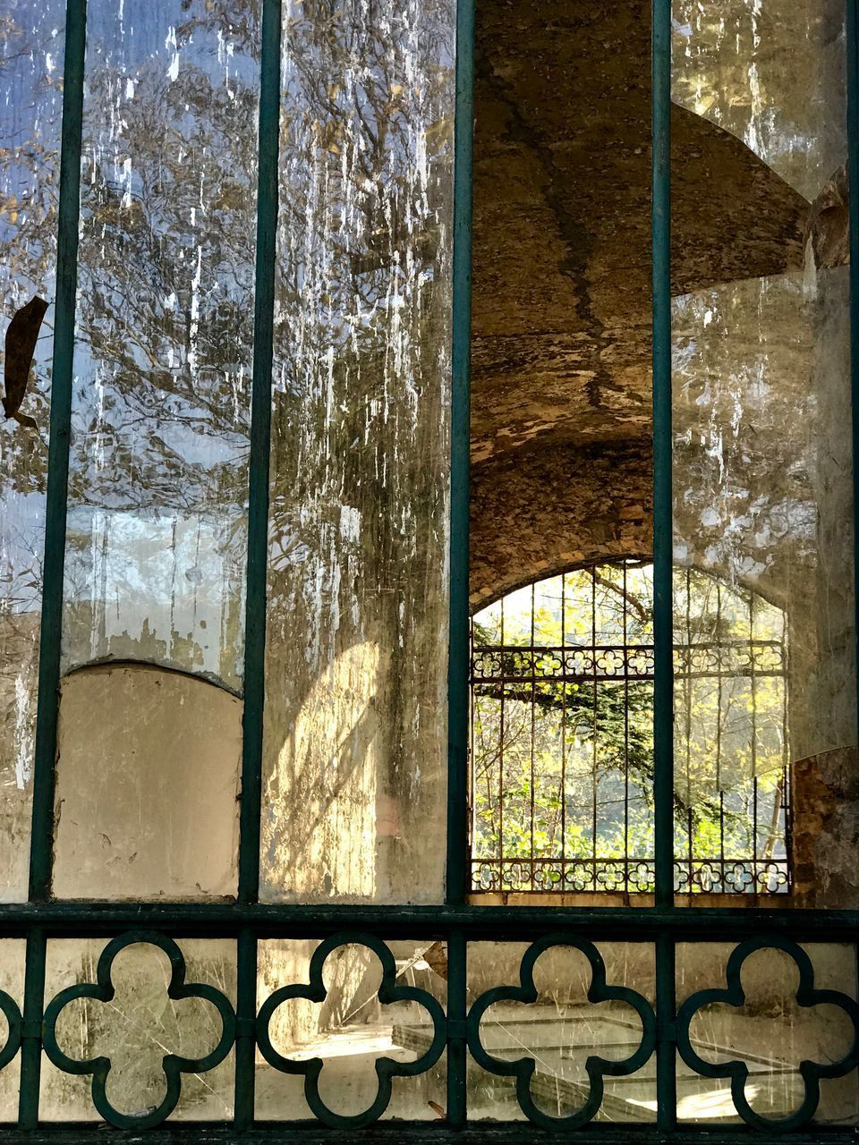 window, glass - material, indoors, no people, architecture, transparent, day, building, built structure, sunlight, nature, history, metal, the past, grate, pattern, tree, grid, railing, glass, wrought iron