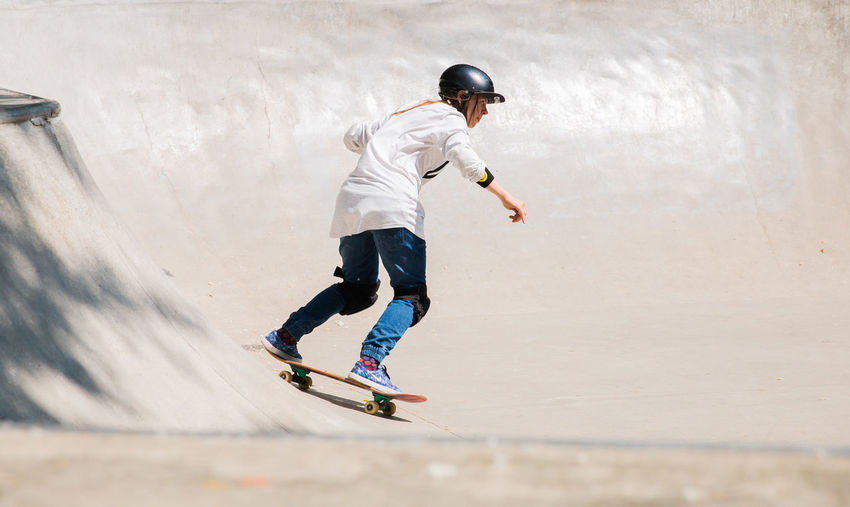 girl skateboarding in a skatepark Full Length Sport Leisure Activity Lifestyles One Person Skill  Casual Clothing Motion Boys Men Real People Child Day Childhood Sports Equipment Balance Skateboard Park Males  Helmet Outdoors Riding