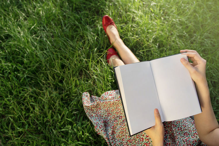 Low section of woman holding book on grassy field