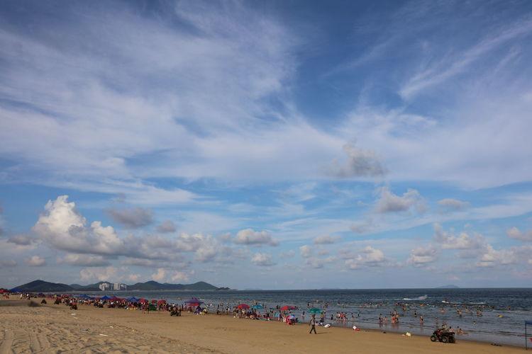 People at seaside against cloudy sky