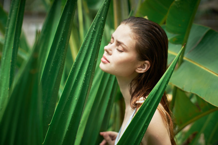 Young woman looking away against plants