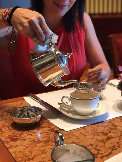 Midsection Of Woman Pouring Tea At Table