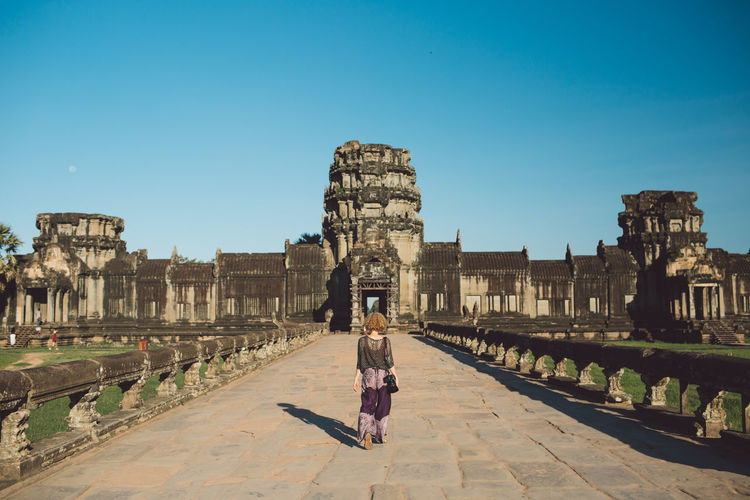 Rear View Of Woman Walking Towards Historical Building Against Blue Sky