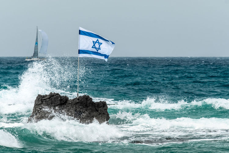 Copy Space Turquoise Colored Aquatic Sport Beauty In Nature Clear Sky Day Flag Horizon Horizon Over Water Israel Motion Nature Nautical Vessel No People Outdoors Power In Nature Regatta Rock Scenics - Nature Sea Sky Sport Water Wave Wind