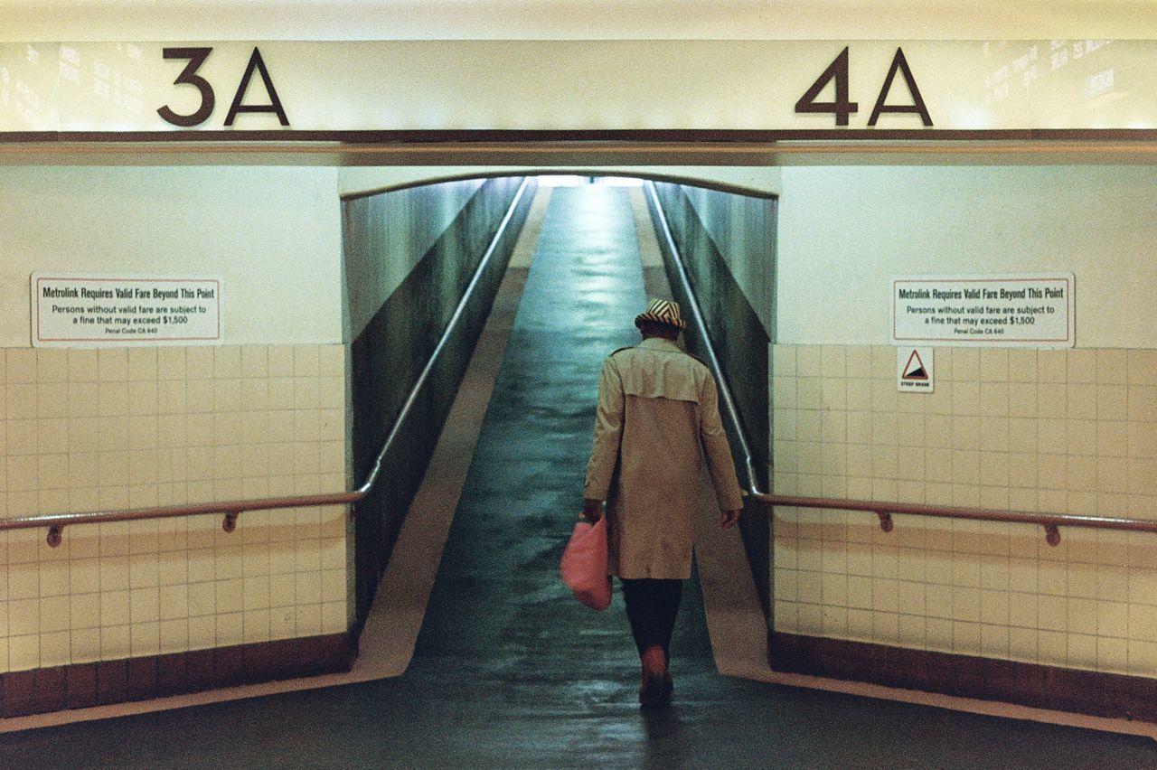 REAR VIEW OF WOMAN WALKING ON SUBWAY PLATFORM