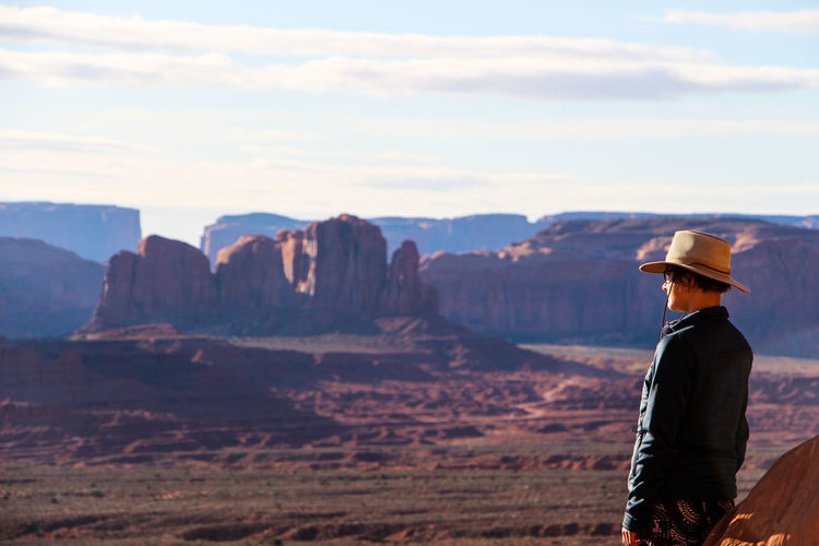 One Person Mountain Scenics - Nature Beauty In Nature Sky Nature Cloud - Sky Standing Non-urban Scene Tranquility Real People Leisure Activity Side View Tranquil Scene Mountain Range Rock Adult Clothing Rock - Object Looking At View Outdoors Arizona Monument Valley