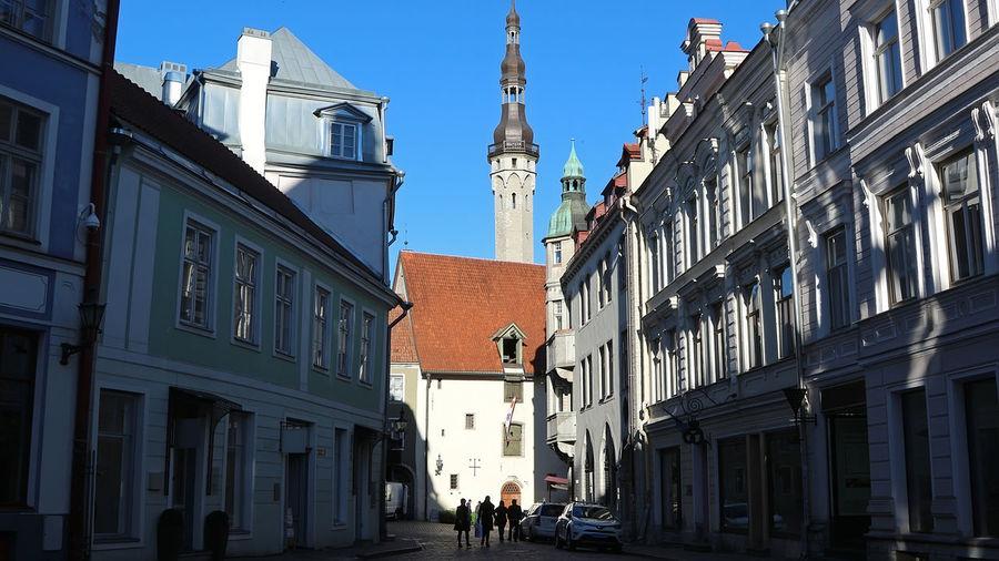 People walking on street amidst buildings against sky in city