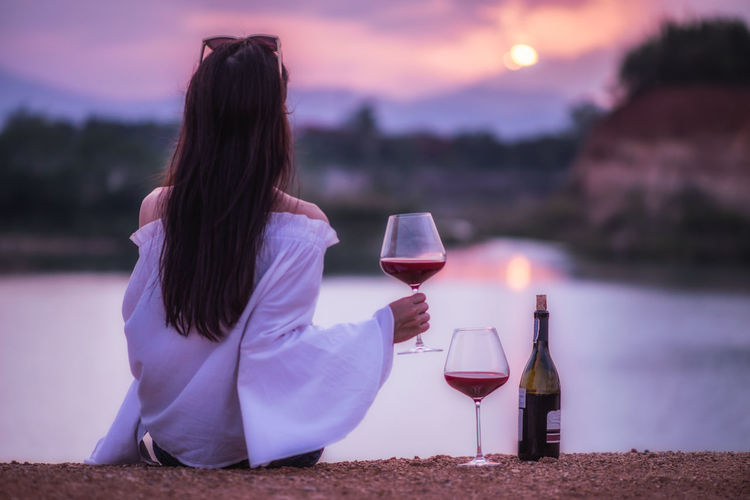 Rear View Of Woman Having Wine While Sitting At Beach During Sunset