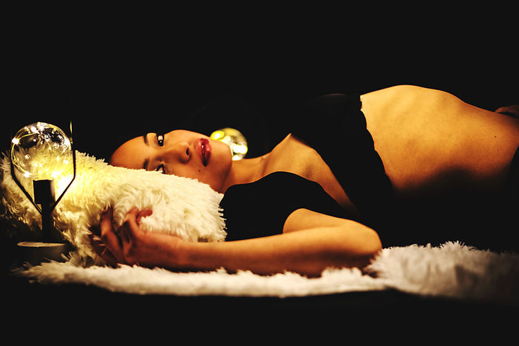 Young woman lying down on bed against black background