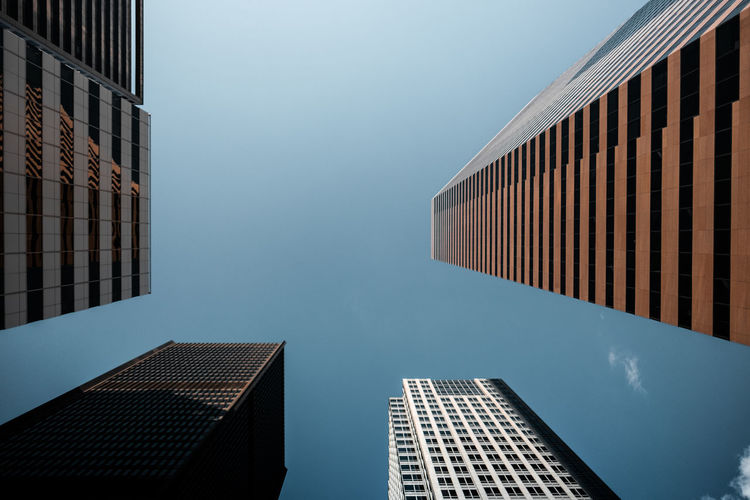 Low angle view of towers against blue sky in city
