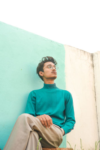 Low angle view of young man looking away against wall