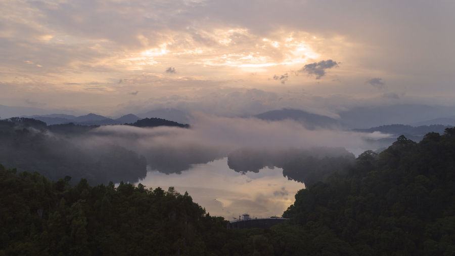 An aerial view of a dam in the morning. Beauty In Nature Cloud - Sky Day Hazy  Idyllic Landscape Mountain Nature Nature, Aerial, Landscape, Green, Background, Travel, View, Tree, Beauty, Forest, Countryside, Beautiful, Tourism, Scenery, Rural, Light, Sunny, Outdoor, Season, Tropical, Field, Environment, Air, Drone, Top, Outdoors, Paradise, Day, Water, Scenic, Wallpa No People Outdoors Scenics Sky Sunset Tranquil Scene Tranquility Tree