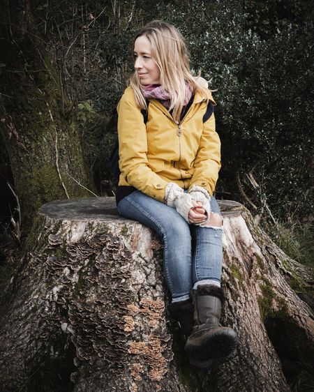 Full length of woman sitting on tree trunk in forest