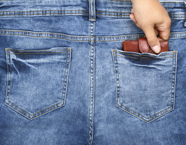 Cropped hand removing wallet from back pocket of jeans