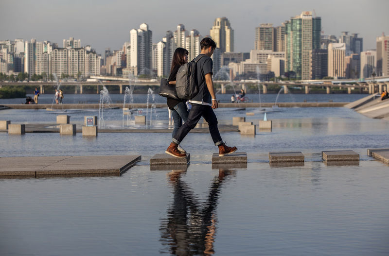 Architecture Built Structure Casual Clothing City City Life Cityscape Day Full Length Han River Hangang Park Jumping Leisure Activity Lifestyles Motion Outdoors River Sky Tourism Walking Water