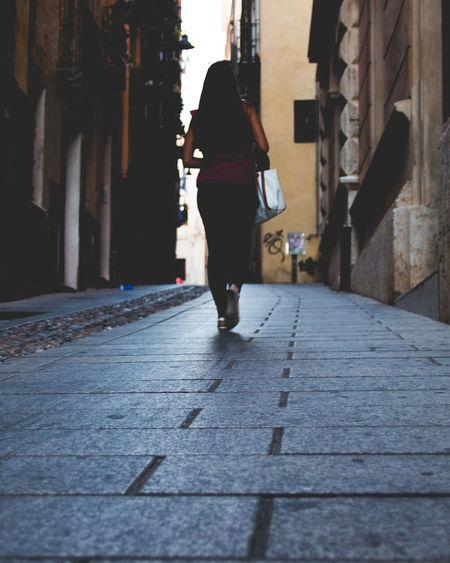 Surface Level Shot Of Woman Walking On Street