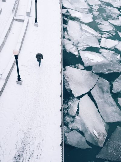 High angle view of man walking on snow covered pathway by icebergs in river