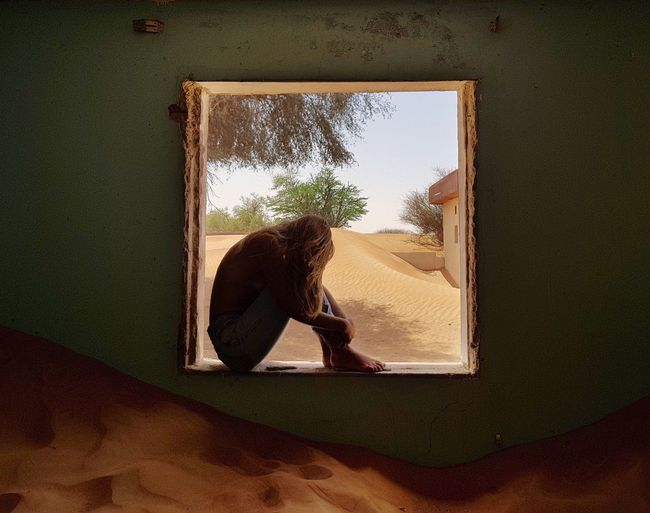 Side View Of Depressed Woman Sitting On Window Sill At Home