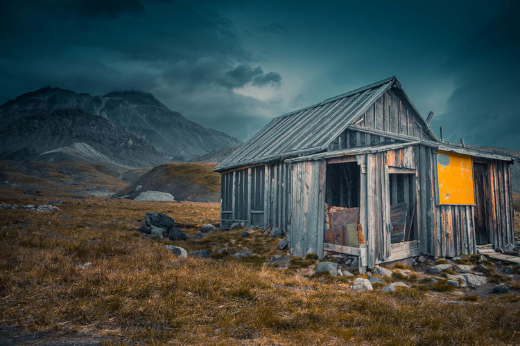 Exterior of abandoned house on mountain against sky