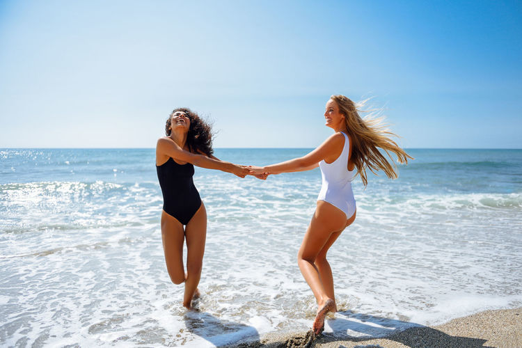 Cheerful friends enjoying at beach during sunny day