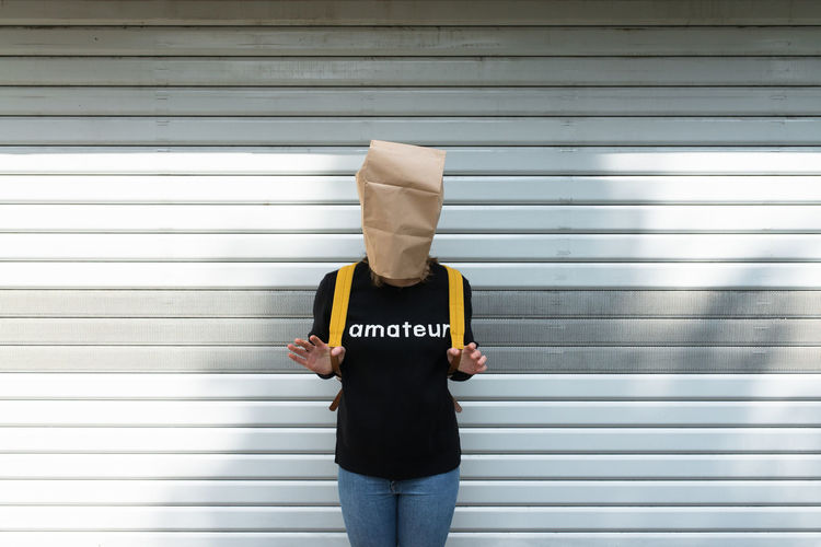 Woman covering face with paper bag while standing against shutter