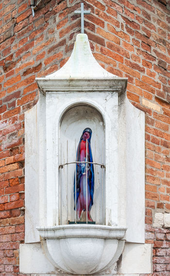 A modern glass religious statue in a window frame in Venice, Italy Cross Glass Art Glass Sculpture Italy 🇮🇹 Venice Italy Architecture Brick Wall Building Exterior Built Structure Close-up Day Glass Statue Human Representation Modern Art No People Outdoors Religion Spirituality Statue Stone Frame Window