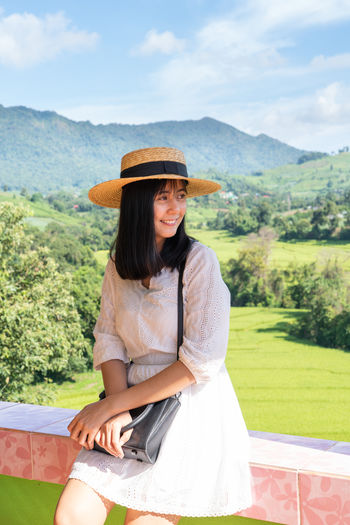 One Person Hat Real People Leisure Activity Mountain Three Quarter Length Clothing Lifestyles Young Adult Day Sitting Nature Young Women Plant Women Casual Clothing Sky Land Field Hair Hairstyle Outdoors Sun Hat Portrait ASIA