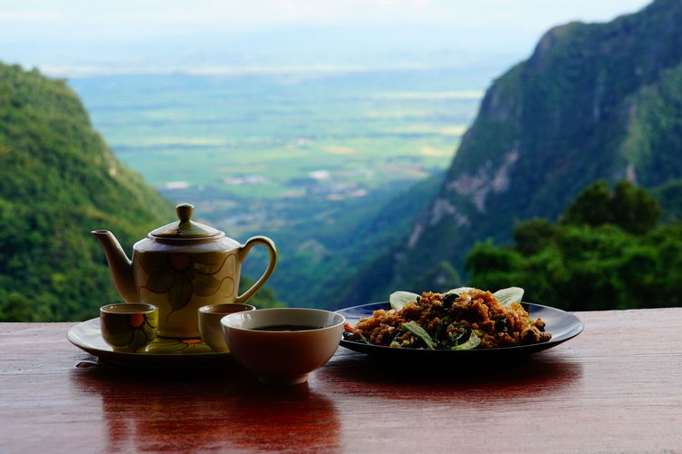 Close-up of tea and food on table against mountains