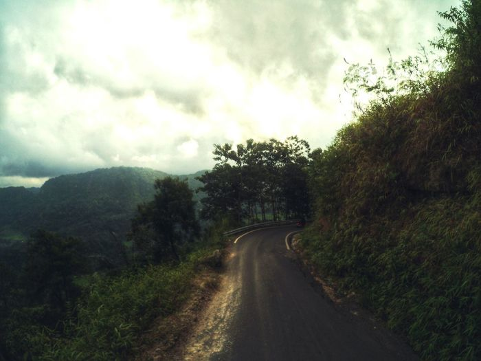 Country road against cloudy sky