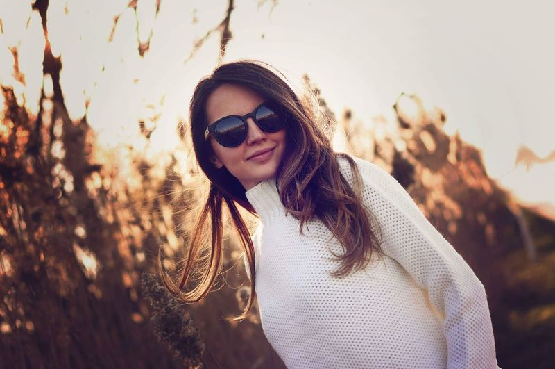 Portrait of young woman wearing sunglasses during sunset