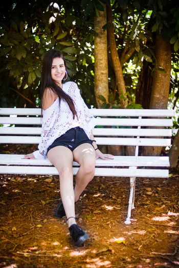 Portrait of smiling young woman sitting on bench