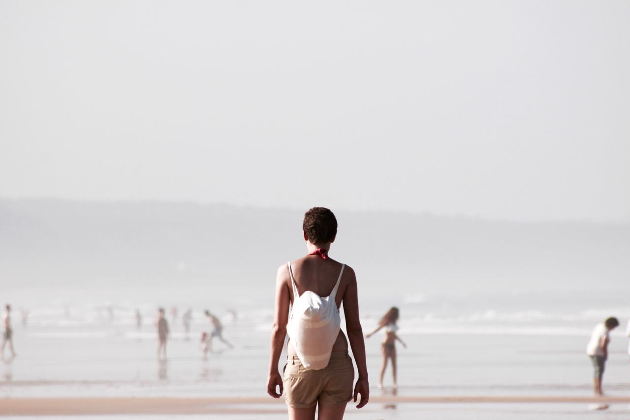 Rear view of woman carrying bag while walking on beach during foggy weather