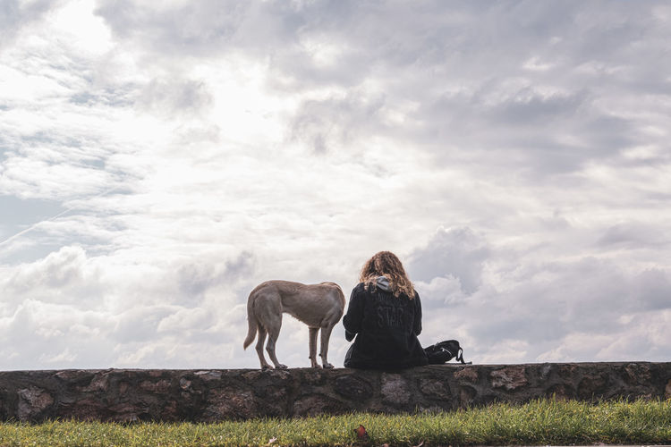 Man with dog sitting on field against sky
