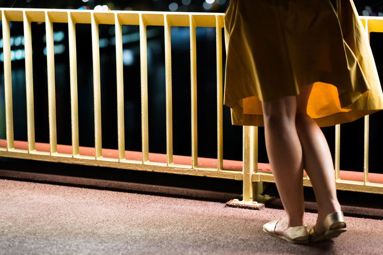 Low Section Of Woman Standing By Railing