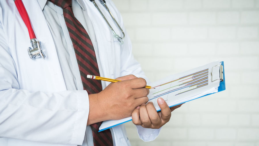 Midsection Of Male Doctor Holding Clipboard While Standing Against Wall