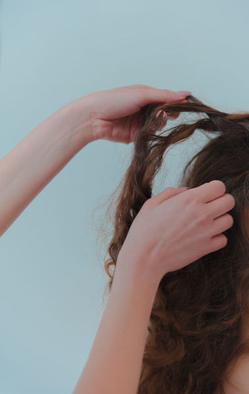 Cropped hands doing hairstyle for woman against wall