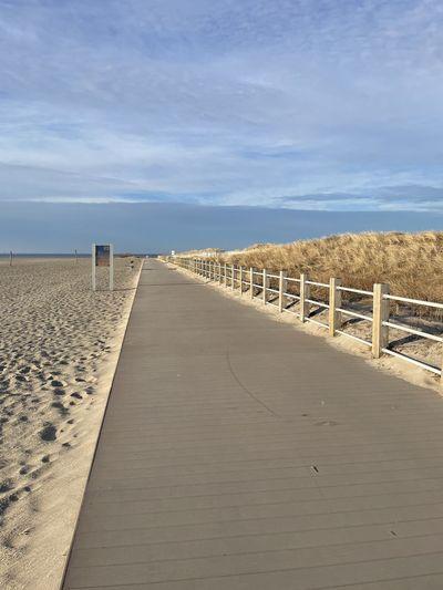 Footpath leading towards beach against sky
