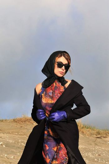 Young woman wearing sunglasses standing on land against sky