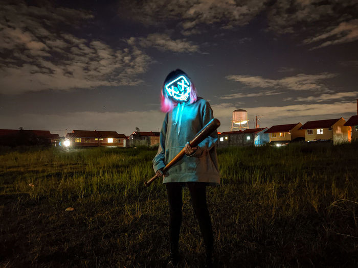 Man standing on field at night