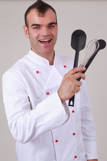 Portrait of happy chef holding kitchen utensils while standing against gray background