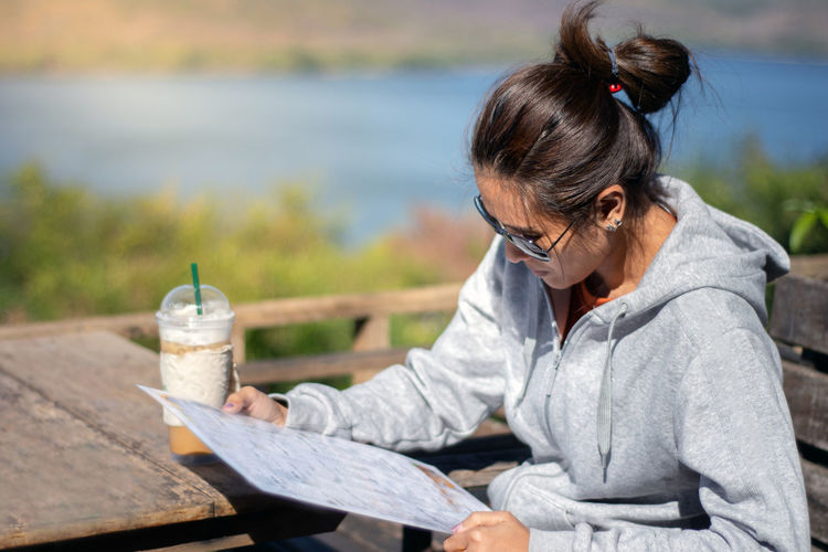 Woman reading menu while sitting on table at restaurant