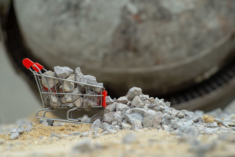 Selective focus on shopping trolley carries the crushed stones and pouring onto the pile at the construction site Selective Focus Container Basket Shopping Cart Wheel Construction Site Toy Preparation